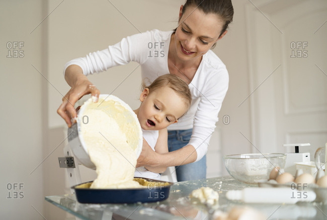 Mother and little daughter making a cake together pouring batter into baking pan