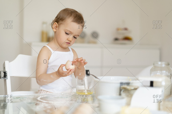 Girl making a cake in kitchen at home cracking an egg