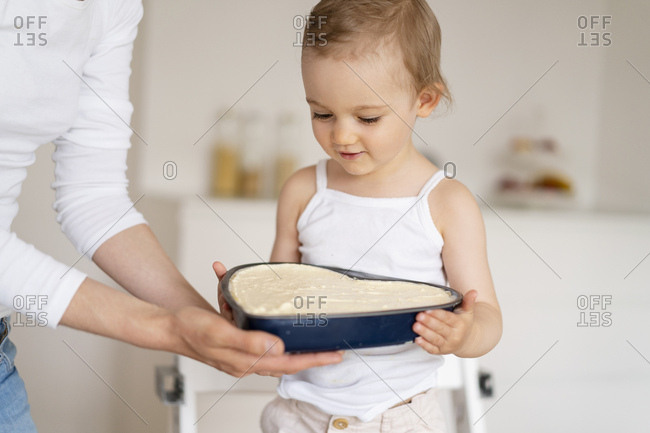 Little girl and mother holding a baking pan with cake batter together in kitchen at home