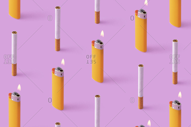 Rows of cigarettes and burning lighters on purple background