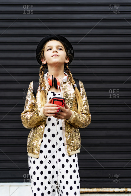 Portrait of girl with smartphone wearing hat- golden sequin jacket and polka dot jumpsuit thinking