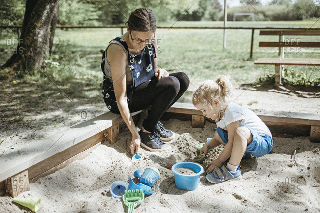 Mother playing with little daughter in sandbox on a playground
