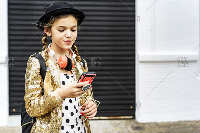 Portrait of girl with headphones wearing hat and golden sequin jacket looking at cell phone