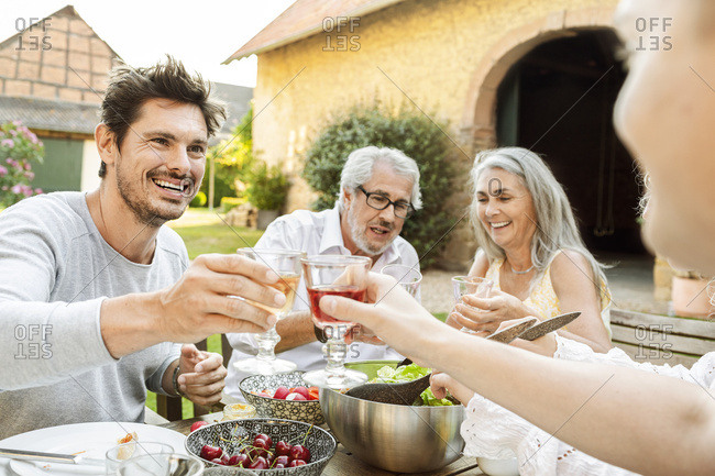Happy family eating together in the garden- clinking glasses
