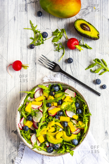 Bowl of rocket salad with mango- avocado- red radishes and blueberries