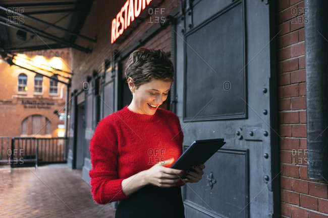 Germany- Berlin- smiling restaurant manager using digital tablet outdoors