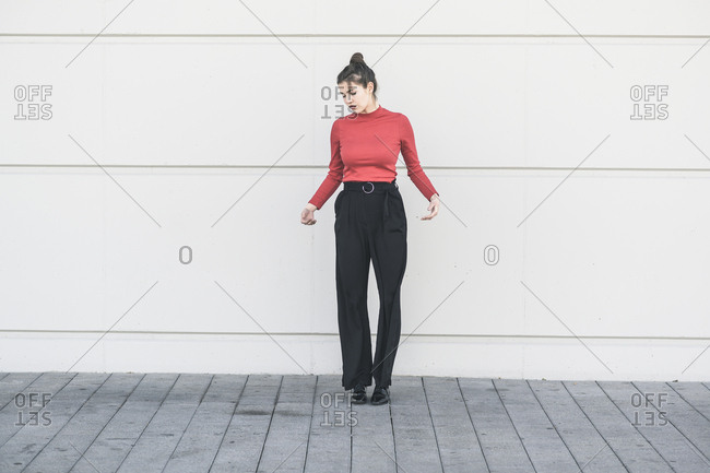 Elegant young woman standing at a wall