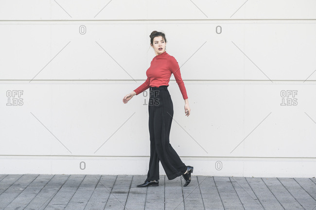 Elegant young walking along a wall