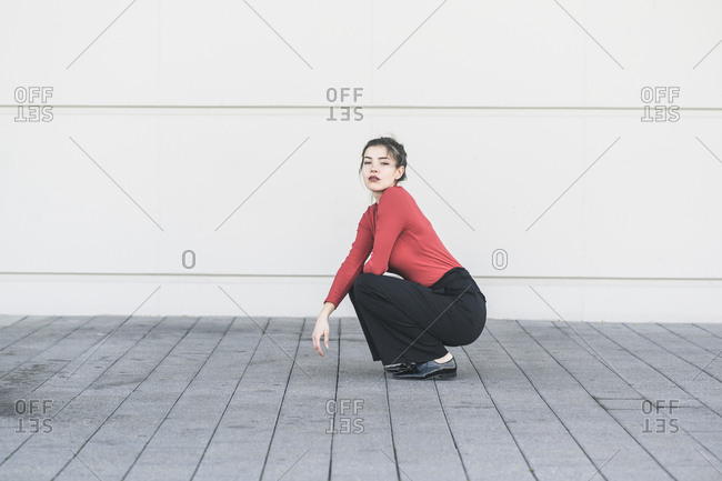 Elegant young woman crouching in front of a wall