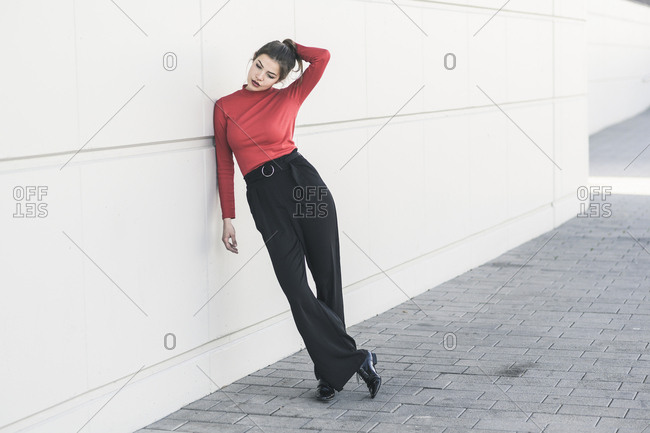 Elegant young woman leaning against a wall