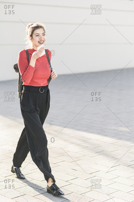 Happy young woman using smartphone in the city