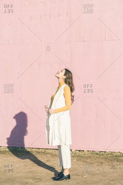 Happy young woman enjoying the sunshine in front of a pink wall