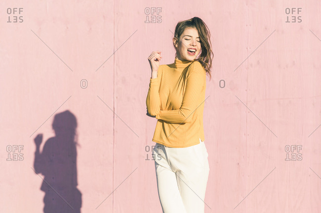 Happy young woman in front of a pink wall