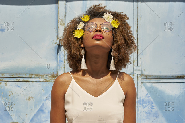 Portrait of young woman with red lips wearing glasses and flowers in her hair looking up