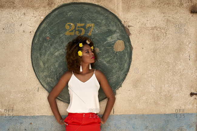 Self-confident young woman leaning against wall looking around