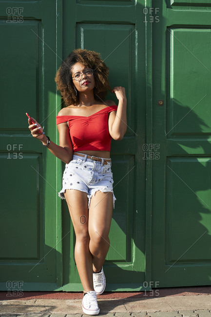 Woman in red with her phone at green door