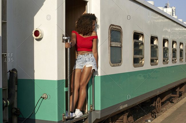 Woman standing at the door of a train looking around