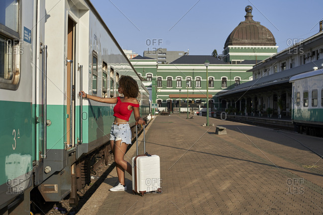 Woman with suitcase at train station getting into train