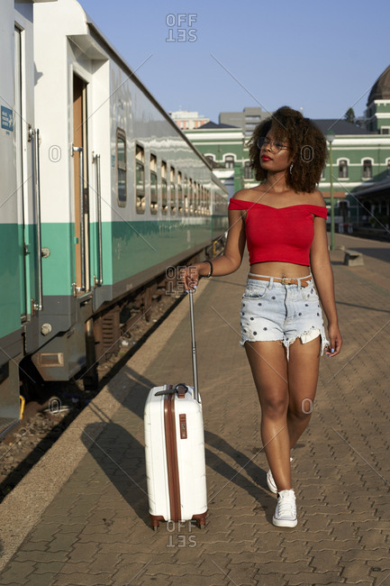 Woman walking with her suitcase at train station