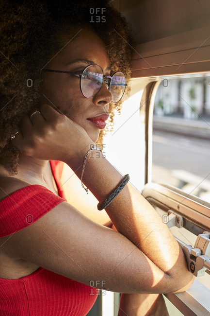 Young woman on a train looking out of window