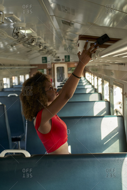 Young woman placing her suitcase in a train