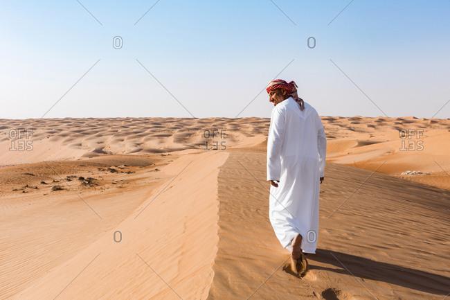 Bedouin walking in the desert- Wahiba Sands- oman