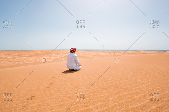 Bedouin in National dress praying in the desert- rear view- Wahiba Sands- Oman