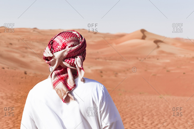 Bedouin in National dress standing in the desert- rear view- Wahiba Sands- Oman