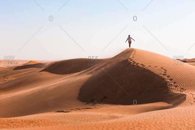 Man walking on a sand dune- Wahiba Sands- Oman