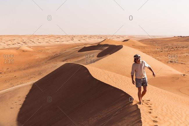 Man walking on a sand dune- Wahiba Sands- Oman