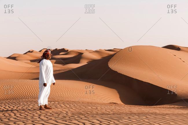 Bedouin in National dress standing in the desert- Wahiba Sands- Oman