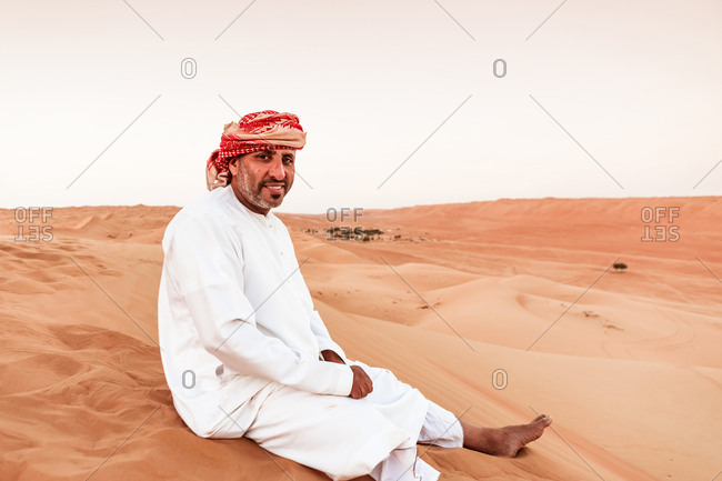 Bedouin in National dress sitting on sand dune in the desert- Wahiba Sands- Oman