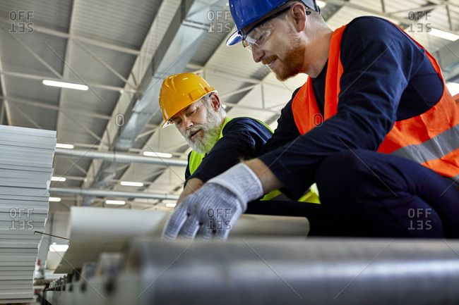 Two men working on plan in factory