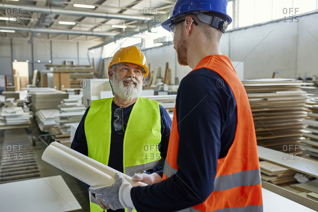 Two men with plan talking in factory