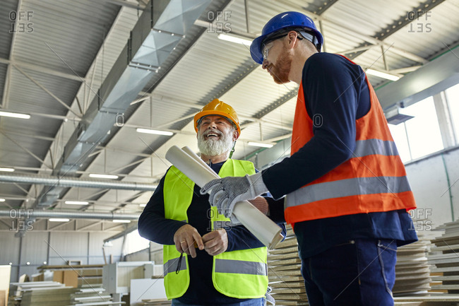 Laughing worker with colleague in factory