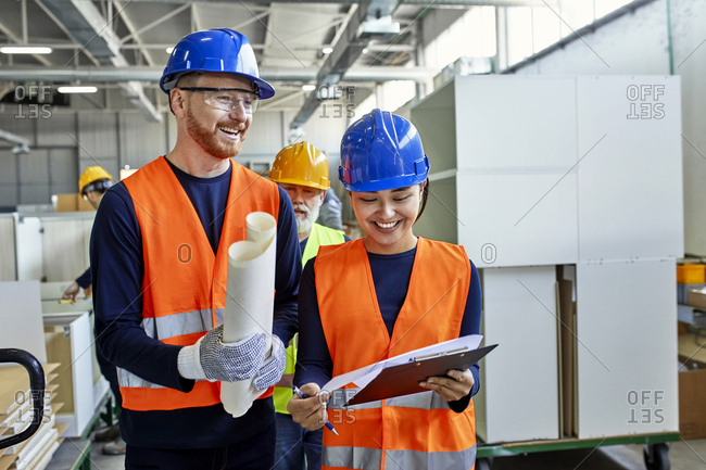 Happy colleagues in protective work wear talking in factory