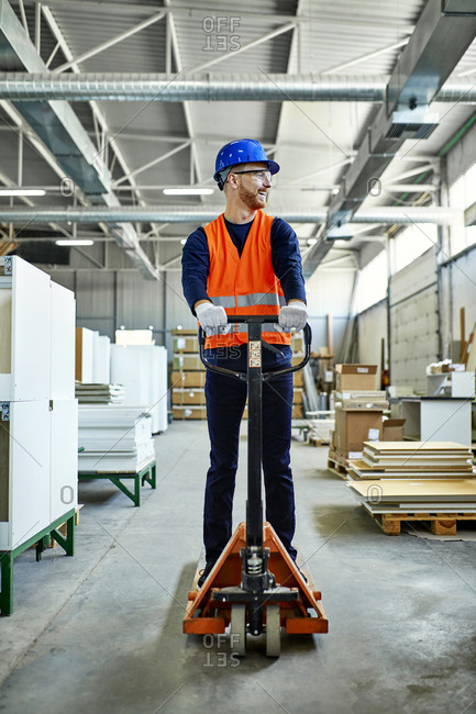 Worker riding on pallet jack in factory