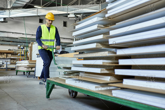 Worker pulling pallet jack with wooden boards in factory