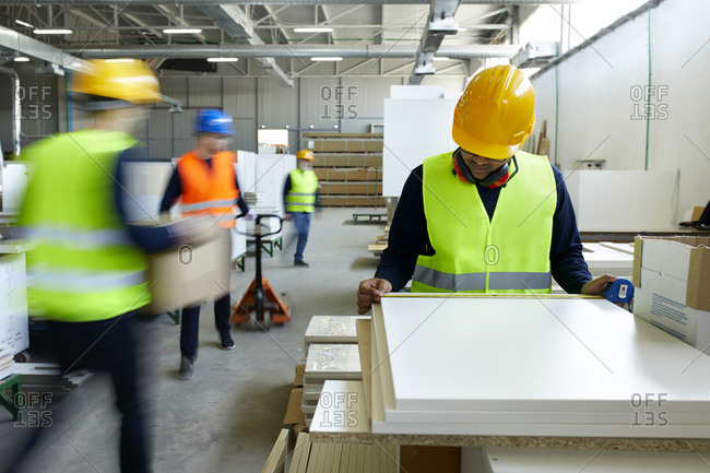Worker examining wooden boards in factory with colleagues moving in background