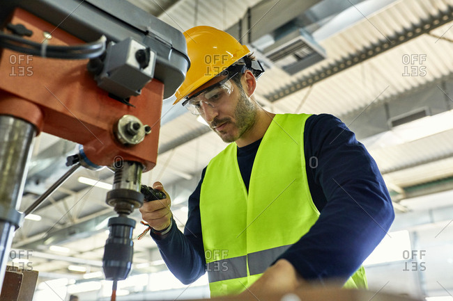 Worker operating drill in factory