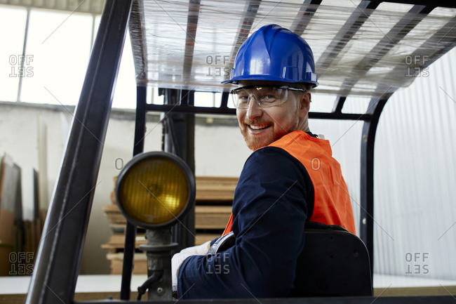 Portrait of smiling worker on forklift in factory