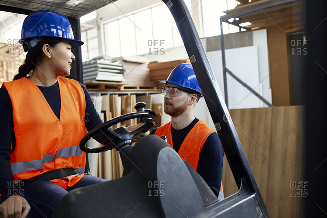Man talking to female worker on forklift in factory