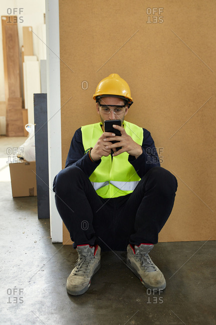 Worker using cell phone during a break in factory