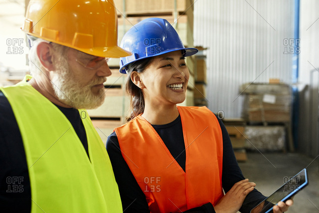 Male and female worker with tablet working together in factory