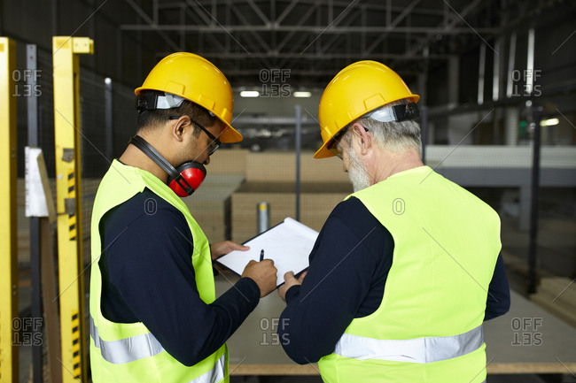 Two men signing document in factory warehouse