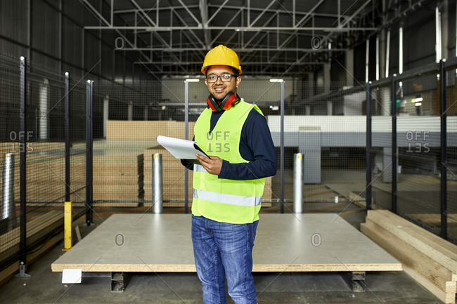 Portrait of smiling worker with clipboard in factory warehouse