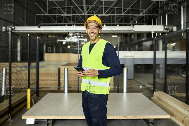 Portrait of smiling worker with tablet in factory warehouse