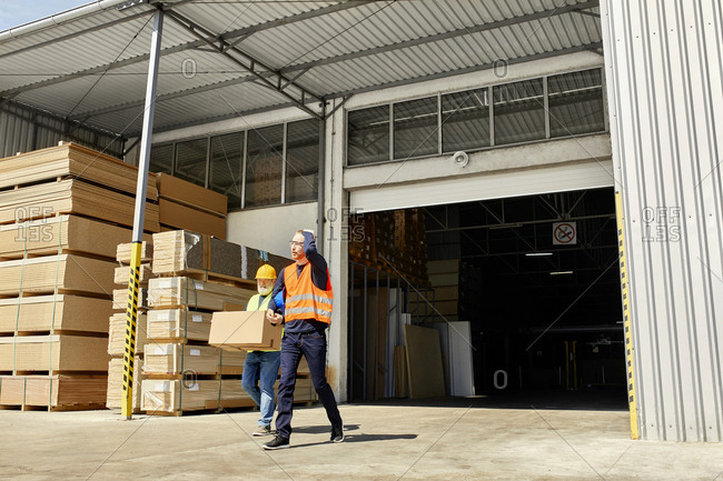 Two workers with box walking on factory yard