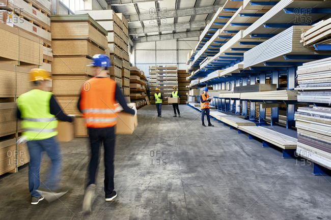Workers moving and carrying boxes in factory warehouse