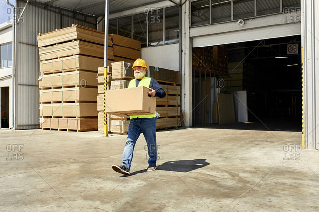 Worker carrying box on factory yard
